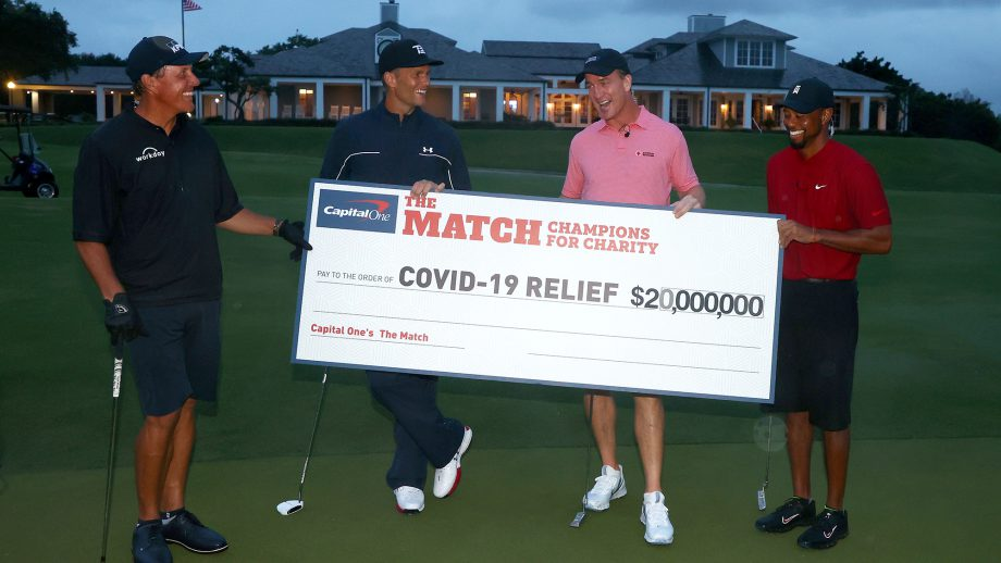 Tiger Woods and former NFL player Peyton Manning celebrate defeating Phil Mickelson and NFL player Tom Brady of the Tampa Bay Buccaneers on the 18th green during The Match: Champions For Charity