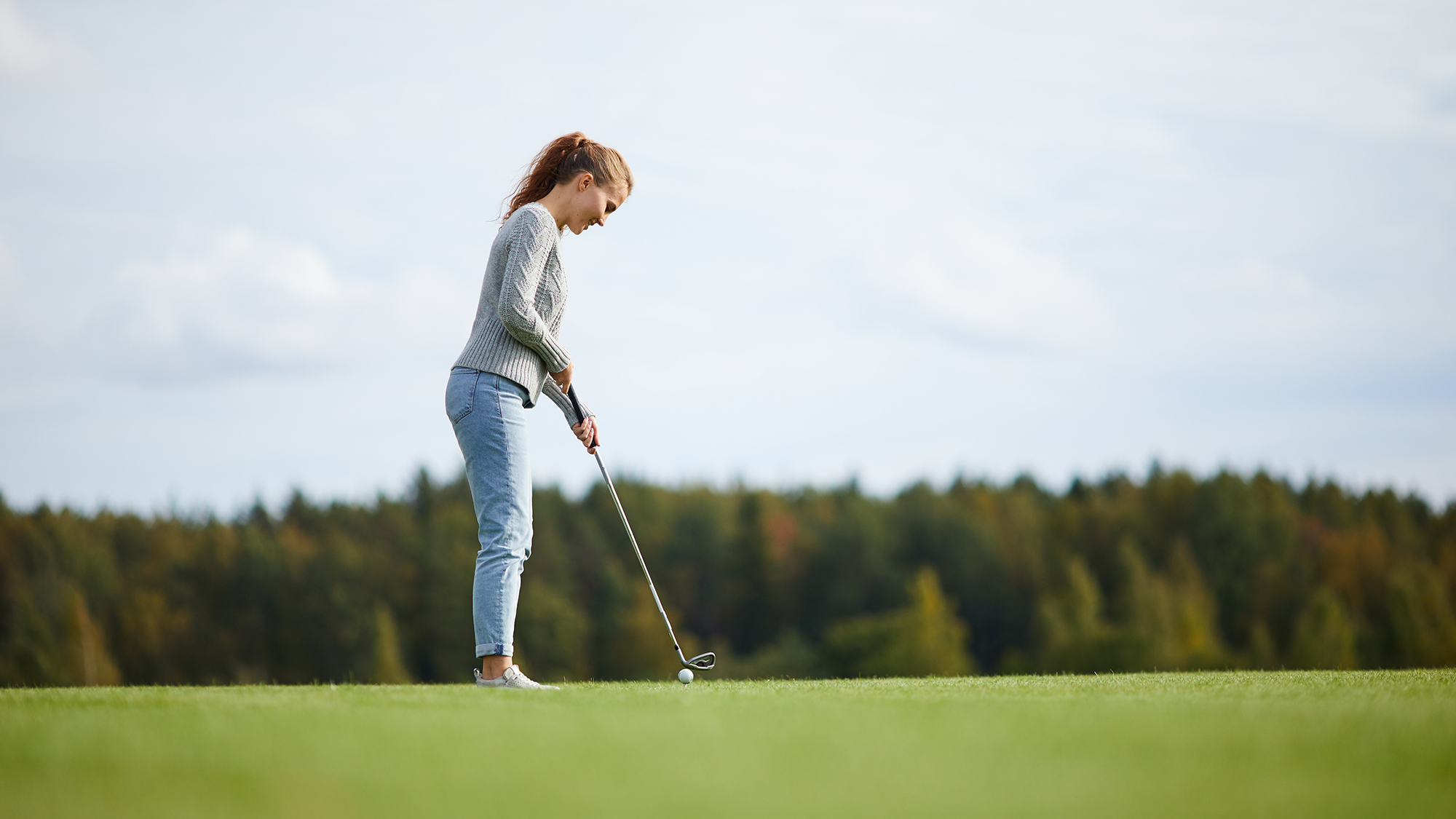 Young active woman in casualwear standing on golf field and getting ready to hit ball with club