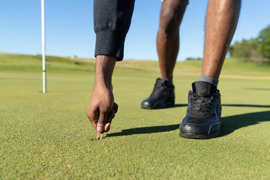 Golfer fixing ball mark